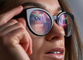 Kursy walut i wykresy odbijające się w okularach kobiety